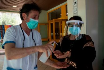 A woman wearing a face mask and shield is helped sanitize her hands as she arrives on May 6, 2020 at the Tor Vergata Covid hospital in Rome, during the country's lockdown aimed at curbing the spread of the COVID-19 infection, caused by the novel coronavirus. (Photo by Tiziana FABI / AFP) (Photo by TIZIANA FABI/AFP via Getty Images)