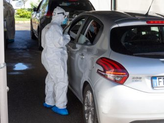MILAN, ITALY - JUNE 05: A nurse, wearing a protective suit, offers a mouth and nose swab through a car window at a 'drive-through' coronavirus testing facility at Ospedale San Raffaele Milan, Italy. Many Italian businesses have been allowed to reopen, after more than two months of a nationwide lockdown meant to curb the spread of Covid-19.  (Photo by Pietro D'Aprano/Getty Images)