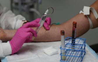 HOLLYWOOD, FLORIDA - AUGUST 07: Leyda Valentine, an assistant coordinator, takes blood from Lisa Taylor as she participates in a COVID-19 vaccination study at Research Centers of America on August 07, 2020 in Hollywood, Florida.  Research Centers of America is currently conducting COVID-19 vaccine trials, implemented under the federal government's Operation Warp Speed program. The center is recruiting volunteers to participate in the clinical trials, working with the Federal Government and major Pharmaceutical Companies, that are racing to develop a vaccine to potentially prevent COVID-19.  (Photo by Joe Raedle/Getty Images)