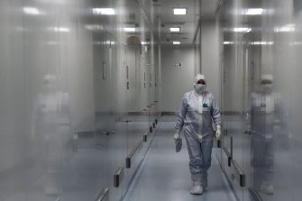 An employee wearing protective equipment walks in a passage at the headquarters of Russia's biotech company BIOCAD, which is developing its own vaccine against the new coronavirus and working on another one in cooperation with the country's virus research centre in Siberia, Vektor, in Strelna on May 20, 2020. (Photo by OLGA MALTSEVA / AFP) (Photo by OLGA MALTSEVA/AFP via Getty Images)