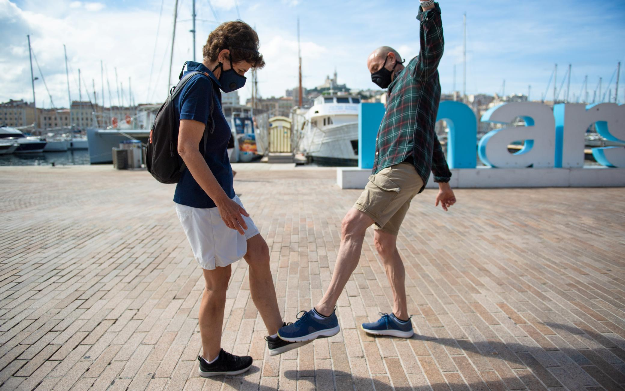 A man and a woman pose as they greet each other with their feet in the Vieux Port of Marseille southern France, on May 17, 2020, in order to use new social distanciation gesture to salute people as a prophylactic measure against the spread of the Covid-19 disease caused by the novel coronavirus. (Photo by CLEMENT MAHOUDEAU / AFP) (Photo by CLEMENT MAHOUDEAU/AFP via Getty Images)
