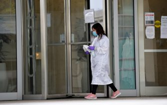 A women cleans the entrance doors to Moderna headquarters in Cambridge, Massachusetts on May 18, 2020. - US biotech firm Moderna reported promising early results from the first clinical tests of an experimental vaccine against the novel coronavirus performed on a small number of volunteers. The Cambridge, Massachusetts-based company said the vaccine candidate, mRNA-1273, appeared to produce an immune response in eight people who received it similar to that seen in people convalescing from the virus. (Photo by Joseph Prezioso / AFP) (Photo by JOSEPH PREZIOSO/AFP via Getty Images)