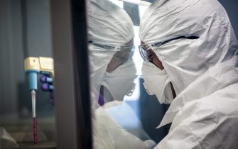 """A scientist is at work in the VirPath university laboratory, classified as """"P3"""" level of safety, on February 5, 2020 as they try to find an effective treatment against the new SARS-like coronavirus, which has already caused more than 560 deaths. - When most are busy developing vaccines or testing the few anti-virals available, VirPath will go after drugs used for diseases that have nothing to do with a respiratory infection such as 2019-nCoV. (Photo by JEFF PACHOUD / AFP) (Photo by JEFF PACHOUD/AFP via Getty Images)"""