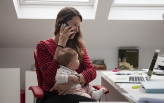 """MAJADAHONDA, MADRID, SPAIN - MAY 11. Virginia Bejar, the photographer's partner, strives to work at home while holding her six-month-old daughter Olivia, also the photographer's daughter, during the Covid-19 lockdown on May 11, 2020, in Majadahonda, Madrid, Spain. Some parts of Spain have entered """"Phase One"""" of transition from the coronavirus lockdown, allowing many shops to reopen as well as restaurants who serve customers outdoors. Locations that were harder hit by coronavirus (COVID-19), such as Madrid and Barcelona, remain in a stricter """"Phase 0"""" quarantine. Across the country workers who can do their jobs from home like Bejar are obliged to do so. In fact, most business offices still remain closed. (Photo by Miguel Pereira/Getty Images)"""