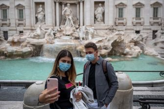ROME, ITALY - OCTOBER 02: People wearing protective masks walk around the Fontana di Trevi (Trevi Fountain) amid Covid-19 pandemic, on October 02, 2020 in Rome, Italy. The Lazio region President Nicola Zingaretti set an order obliging people to wear face masks in public including outdoors due to the increase of Covid-19 cases in the Lazio region. (Photo by Antonio Masiello/Getty Images)