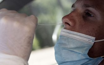 A man undergoes a swab test for coronavirus at a drive-through testing site of the Santa Maria della Pieta hospital in Rome on August 18, 2020. - On August 16, Italy suspended its discos and ordered the mandatory wearing of masks from 6:00pm (1600 GMT) to 6:00am to clamp down on the spread of infection among young people, less than a month before the restart of school. (Photo by Tiziana FABI / AFP) (Photo by TIZIANA FABI/AFP via Getty Images)