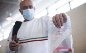 CASELLE TORINESE, ITALY - AUGUST 26: A man wearing protective mask shows a personal swabs test kit on August 26, 2020 in Turin, Italy. At Italian airports, all travelers from countries at risk of Covid-19 are tested with swabs to prevent the spread of Covid 19 in Italy. (Photo by Stefano Guidi/Getty Images)