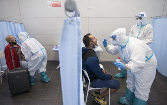 CASELLE TORINESE, ITALY - AUGUST 26: General view of medical staff in full PPE conduct a swab test on travelers after their flight from Ibiza, Spain to Turin on August 26, 2020 in Turin, Italy. At Italian airports, all travelers from countries at risk of Covid-19 are tested with swabs to prevent the spread of Covid 19 in Italy. (Photo by Stefano Guidi/Getty Images)