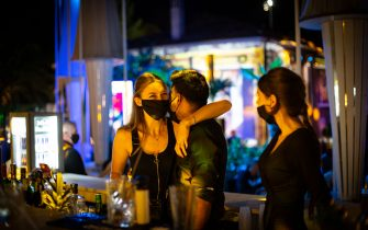 """RIMINI, ITALY - JUNE 20: Staff in face masks greet each other at the bar area on the opening of the summer season for """"Villa delle Rose"""", one of the most famous clubs on the Adriatic Coast on June 20, 2020 in Rimini, Italy. The Villa delle Rose is among the first dance clubs to reopen in the Adriatic Riviera after the Covid-19 pandemic. (Photo by Max Cavallari/Getty Images)"""