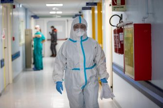 A member of medical staff wearing a personal protective equipment (PPE) walks in the Intensive Care Unit (ICU) for the novel coronavirus, COVID-19 cases, in the San Filippo Neri hospital in Rome, on October 29, 2020. - Italy's Prime Minister Giuseppe Conte tightened nationwide coronavirus restrictions after the country registered a record number of new cases, despite opposition from regional heads and street protests over curfews.  ANSA/MASSIMO PERCOSSI