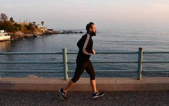 Un runner sulle strade deserte a Genova dopo il rafforzamento delle misure del Governo per contenere il contaggio da Covid-19. Genova, 21 Marzo 2020ANSA/LUCA ZENNARO