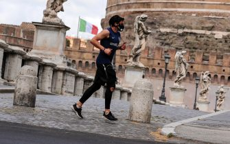 A runner with a protective mask passes by SantÕAngelo Bridge during the coronavirus lockdown in Rome, Italy, 29 April 2020. ANSA/RICCARDO ANTIMIANI