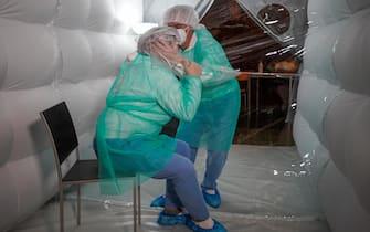 L'abbraccio protetto nella simulazione degli operatori, nella fase di collaudo. San Mauro Torinese, Torino, 4 dicembre 2020 ANSA/JESSICA PASQUALON