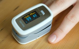 BERLIN, GERMANY - APRIL 28: In this photo illustration, a young woman uses an oximeter to measure her pulse and her peripheral oxygen saturation level during the coronavirus crisis on April 28, 2020 in Berlin, Germany. The device is useful in checking for low or declining oxygen saturation, which might indicate onsetting pneumonia, a common condition among Covid-19 patients who wind up in intensive care.   (Photo by Sean Gallup/Getty Images)