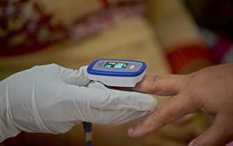A health worker uses a fingertip pulse oximeter at a screening camp for residents to test for COVID-19 coronavirus, in Mumbai on August 17, 2020. - India's death toll from the coronavirus hit 50,000 on August 17, with more than 900 new fatalities reported in 24 hours, health ministry data showed. (Photo by Indranil MUKHERJEE / AFP) (Photo by INDRANIL MUKHERJEE/AFP via Getty Images)