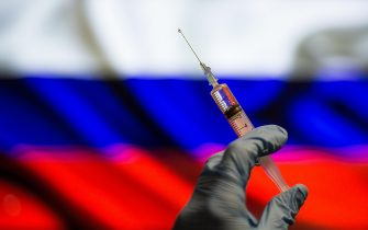 In this photo illustration a close up of a hand holding a medical syringe in front of the Russian Flag. (Photo by Thiago Prudêncio / SOPA Images/Sipa USA)