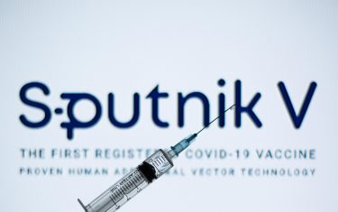 In this photo illustration a medical syringe seen displayed in front of the Sputnik V logo. (Photo by Thiago Prudêncio / SOPA Images/Sipa USA)