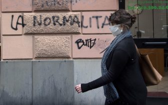 """A woman wearing a protective mask walks next an inscription painted on  the wall of a building reading in italian """"normality"""", Genoa, Italy, 21 April 2020. Italian Prime Minister Giuseppe Conte, during his speech to the Chambers, said that the masks and the social security distancing will be maintained until a vaccine against Covid-19 wil not be discovered. ANSA/LUCA ZENNARO"""