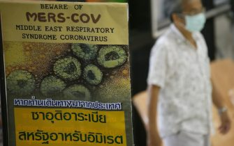 epa05122136 A Thai man wears a protective mask as he walks next to a sign giving information on Middle East Respiratory Syndrome (MERS), at the Bamrasbaradura Infectious Diseases Institute, Nonthaburi province, on the outskirts of Bangkok, Thailand, 24 January 2016. Thailand identified its second case of Middle Eastern Respiratory Syndrome (MERS), the public health minister said on 24 January 2016. The patient, a 71-year-old man from Oman, arrived in Thailand on 22 January, and was quarantined at an infectious diseases institute. Thai health authorities were working to track down people who might have had contact with the man, including airline passengers and crew and a taxi driver, Public Health Minister Piyasakol Sakolsatayadorn said.  EPA/NARONG SANGNAK
