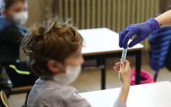Un bambino si sottopone a un test salivare in una scuola di Travagliato, vicino a Brescia