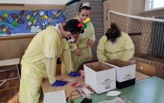 Operato impegnati nella preparazione di test salivari in una scuola materna di Fiumicino