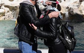 Una giovane coppia si bacia con le mascherine anti coronavirus