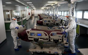 Nurses work to prepare the Intensive care unit in the new Covid-19 Hospital on March 29, 2020 in Verduno, near Alba, Northwestern Italy on the eve of its official opening, as part of the measures taken to fight against the spread of the novel coronavirus. - The hospital have seven beds of intensive care and fifty beds for patients infected by the COVID-19. (Photo by MARCO BERTORELLO / AFP)