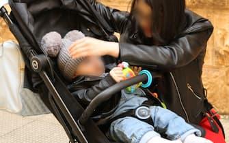 Una mamma col figlio sul passeggino