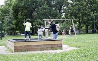 Bimbi giocano con la mamma in un parco