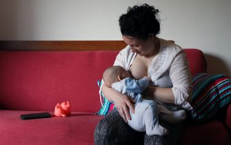 ROME, ITALY - MAY 14: Alessia breastfeeds her son Cosmo on May 14, 2020 in Rome, Italy. The Adduci - Filipponi family is made up of Alessia, 37 years old, architect, and her husband Federico Filipponi, 35 years old and their 3-month-old son Cosmo. Due to her pregnancy and the current situation, Alessia has lost her job and spends most of her time making free protective masks to give to people in need who cannot afford to buy them and take care of her son. Federico, who is an environmental researcher, is injured at home after a serious bike accident. As restrictions are lifted and some Italians are allowed to return to work, schools and daycares remain closed, leaving working parents in a difficult situation. This especially affects mothers, who, according to gender inequality studies, are more often caregivers in Italy's patriarchal society and must choose between their children and their careers. (Photo by Marco Di Lauro/Getty Images)