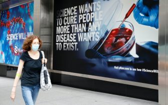epa09473881 A woman wearing a mask walks past a sign outside the headquarters of the pharmaceutical company Pfizer in New York, New York, USA, 17 September 2021. Vaccine advisers for the US Food and Drug Administration (FDA) are meeting on 17 September to discuss whether Americans need another booster shot of the Pfizer/BioNTech Covid-19 vaccine.  EPA/JASON SZENES
