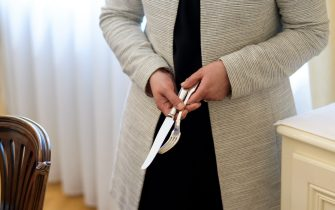 A teacher holds a knife and a fork during a lesson at the Switzerland's last finishing school Institut Villa Pierrefeu on June 26, 2017 in Glion.  Eight women sit primly around an elaborately set table making pleasant small-talk about the weather, as immaculately starched waiting staff stand at the ready. But as one of the servers steps forward holding a silver soup tureen with white-gloved hands, an instructor helps her adjust the angle of the bowl to make sure the ladle is facing the diner. And a second tutor whispers in the ear of another diner to lower her elbow as she brings the spoon to her mouth. The women are not at a fancy restaurant or a high-end social club, but at Switzerland's last finishing school, learning to master good manners, strict etiquette and how to avoid a fatal faux pas. / AFP PHOTO / Fabrice COFFRINI        (Photo credit should read FABRICE COFFRINI/AFP via Getty Images)