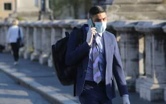 Roma, Italy 6 maggio 2020: Uomo di affari  con la mascherina protettiva ed i guanti al telefono passeggiando per ponte Sant'Angelo a Roma   durante la fase 2 dell'emergenza Covid-19, dopo due mesi di quarantena nella città di Roma. (MARCO IACOBUCCI / IPA/Fotogramma,  - 2020-05-06) p.s. la foto e' utilizzabile nel rispetto del contesto in cui e' stata scattata, e senza intento diffamatorio del decoro delle persone rappresentate