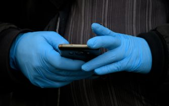 A man wearing gloves as a protective measure, holds a smartphone in Madrid on March 19, 2020. - Spain today announced that deaths from the novel coronavirus had jumped by nearly 30 percent over the past 24 hours to 767. The number of people who have contracted the disease has meanwhile grown by around 25 percent to 17,147, according to health ministry figures, bringing Spain's tally near that of Iran, the world's third most affected country after China and Italy. (Photo by Gabriel BOUYS / AFP) (Photo by GABRIEL BOUYS/AFP via Getty Images)