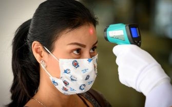A woman, wearing a face mask as a preventive measure against the COVID-19 novel coronavirus, gets her temperature taken before she enters a building in Bangkok on March 17, 2020. (Photo by Mladen ANTONOV / AFP) (Photo by MLADEN ANTONOV/AFP via Getty Images)