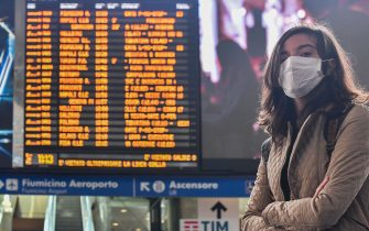 A woman wearing a respiratory mask waits by a timetable at the Termini railway station in Rome on March 10, 2020. - Italy imposed unprecedented national restrictions on its 60 million people on March 10, 2020 to control the deadly coronavirus, as China signalled major progress in its own battle against the global epidemic. (Photo by Tiziana FABI / AFP) (Photo by TIZIANA FABI/AFP via Getty Images)
