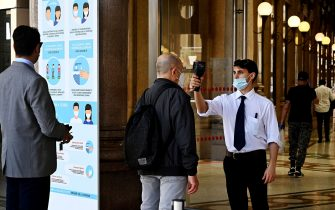 A man (C) undergoes a body temperature scan as he enters the Alberto-Sordi shopping gallery on Via del Corso on May 20, 2020 in central Rome, as the country's is easing its lockdown aimed at curbing the spread of the COVID-19 infection, caused by the novel coronavirus. (Photo by Vincenzo PINTO / AFP) (Photo by VINCENZO PINTO/AFP via Getty Images)