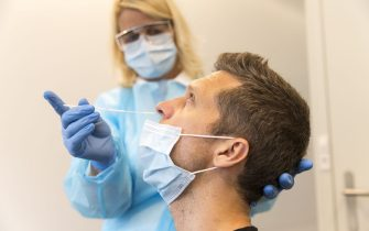 ZURICH, SWITZERLAND - JULY 15: An employee takes a throat swab sample to test for Covid-19 at the COVID-19 Test Center at the University of Zurich during the coronavirus pandemic on July 15, 2020 in Zurich, Switzerland. Switzerland has largely lifted most of its coronavirus lockdown measures and has so far registered approximately 33,000 infections. (Photo by Christian Ender/Getty Images).