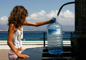 A girl fills a water bottle from a fountain in Messina on August 19, 2009. A heatwave stifled Italy today, with temperatures up to 41 degrees Celsius (106 Fahrenheit) and civil protection authorities issuing warnings for several cities including Rome and Milan. AFP PHOTO / MARCELLO PATERNOSTRO (Photo credit should read MARCELLO PATERNOSTRO/AFP via Getty Images)