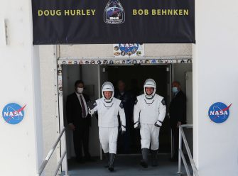 CAPE CANAVERAL, FLORIDA - MAY 30: NASA astronauts Bob Behnken (R) and Doug Hurley walk out of the Operations and Checkout Building on their way to the SpaceX Falcon 9 rocket with the Crew Dragon spacecraft on launch pad 39A at the Kennedy Space Center on May 30, 2020 in Cape Canaveral, Florida. The inaugural flight will be the first manned mission since the end of the Space Shuttle program in 2011 to be launched into space from the United States. (Photo by Joe Raedle/Getty Images)