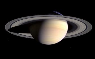 Saturn's peaceful beauty invites the Cassini spacecraft for a closer look in this natural color view, taken during the spacecraft's approach to the planet. By this point in the approach sequence, Saturn was large enough that two narrow angle camera images were required to capture an end-to-end view of the planet, its delicate rings and several of its icy moons. The composite is made entire from these two images.  Moons visible in this mosaic: Epimetheus (116 kilometers, 72 miles across), Pandora (84 kilometers, 52 miles across) and Mimas (398 kilometers, 247 miles across) at left of Saturn; Prometheus (102 kilometers, 63 miles across), Janus (181 kilometers, 113 miles across) and Enceladus (499 kilometers, 310 miles across) at right of Saturn.    (Photo by NASA/WireImage) *** Local Caption ***