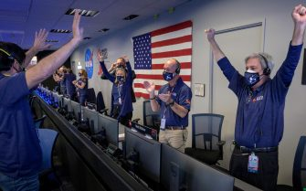 epa09022682 A handout photo made available by NASA shows Members of NASA's Perseverance rover team react in mission control after receiving confirmation the spacecraft successfully touched down on Mars, at NASA's Jet Propulsion Laboratory in Pasadena, California, USA, 18 February 2021. A key objective for Perseverance's mission on Mars is astrobiology, including the search for signs of ancient microbial life. The rover will characterize the planet's geology and past climate, pave the way for human exploration of the Red Planet, and be the first mission to collect and cache Martian rock and regolith.  EPA/NASA/BILL INGALLS HANDOUT MANDATORY CREDIT: (NASA) HANDOUT EDITORIAL USE ONLY/NO SALES