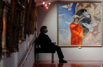 epa09125137 A museum worker sits next to a painting by  Soviet cosmonaut Vladimir Dzhanibekov, titled 'Gagarin before the start', at the Museum of Cosmonautics in Moscow, Russia, 09 April 2021. The museum is dedicated to space exploration, with exhibits, items, and models related to the Soviet and Russian space eras on display. Russia marks the 60th anniversary of the first human spaceflight on 12 April 2021.  EPA/SERGEI ILNITSKY