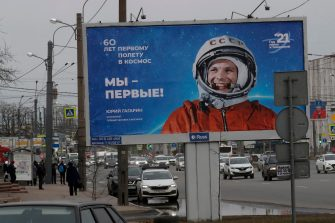 epa09120494 Russian people pass by a poster with a portrait of the first USSR cosmonaut Yuri Gagarin, that reads: 'We are the first' in St. Petersburg, Russia, 07 April 2021. Russia marks the 60th anniversary of the first human spaceflight on April 12.  EPA/ANATOLY MALTSEV