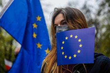 KRAKOW, POLAND - MAY 01: A woman wears a protective face mask and holds an European Union flag to celebrate the 17th anniversary of Poland joining the European Union on May 01, 2021 in Krakow, Poland. Pro-democratic associations and activists gather to march through Krakow streets holding European Union flags to celebrate the 17th anniversary of Poland joining the Union. (Photo by Omar Marques/Getty Images)