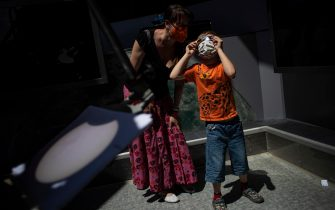 epa09259417 A woman with child observes the partial solar eclipse with special glasses as projection of eclipse from telescope is seen in front, at observatory in Prague, Czech Republic, 10 June 2021. A partial solar eclipse occurs when a portion of the Earth is engulfed by the shadow (penumbera) cast by the Moon as it passes between our planet and the Sun in an imperfect alignment.  EPA/MARTIN DIVISEK