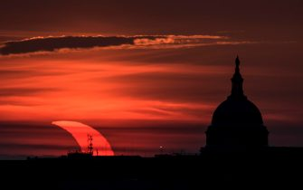 epa09259308 A handout picture made available by the National Aeronautics and Space Administration (NASA) shows a partial solar eclipse as the sun rises to the left of the United States Capitol Building, 10 June 2021, as seen from Arlington, Virginia. The annular or  ring of fire  solar eclipse is only visible to some people in Greenland, Northern Russia, and Canada.  EPA/NASA HANDOUT / Bill Ingalls  HANDOUT EDITORIAL USE ONLY/NO SALES