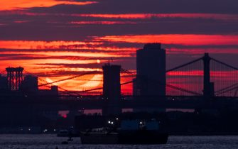 epa09259325 A partial solar eclipse rises over bridges crossing the East River in New York, New York, USA, 10 June 2021. A partial solar eclipse occurs when a portion of the Earth is engulfed by the shadow (penumbera) cast by the Moon as it passes between our planet and the Sun in an imperfect alignment.  EPA/JUSTIN LANE