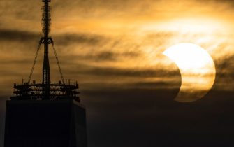 epa09259323 A partial solar eclipse rises over One World Trade Center in New York, New York, USA, 10 June 2021. A partial solar eclipse occurs when a portion of the Earth is engulfed by the shadow (penumbera) cast by the Moon as it passes between our planet and the Sun in an imperfect alignment.  EPA/JUSTIN LANE