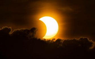 epa09259324 A partial solar eclipse rises New York, New York, USA, 10 June 2021. A partial solar eclipse occurs when a portion of the Earth is engulfed by the shadow (penumbera) cast by the Moon as it passes between our planet and the Sun in an imperfect alignment.  EPA/JUSTIN LANE